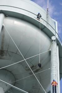 Tom Waters (EPA TSC) hoisting sampling equipment to the lower platform of the tank.